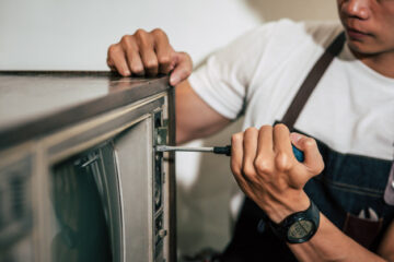 mecanicien-utilise-tournevis-pour-serrer-vis-du-televiseur